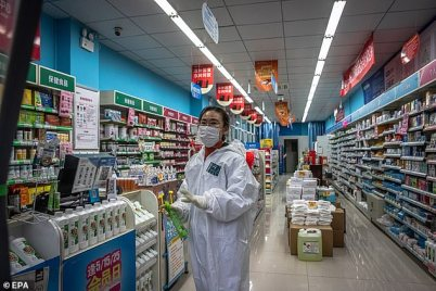 Wuhan locals claim coronavirus has killed 42,000 people in the city alone, more than ten times the national figure claimed by Chinese authorities. Pictured: A worker in a pharmacy in Wuhan today