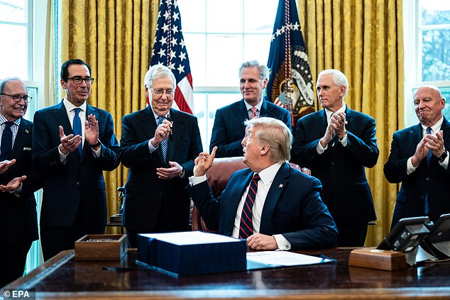 President Donald J. Trump (C) during a signing ceremony for the The CARES Act in the Oval Office at the White House in Washington, DC on March 27. The CARES Act, is a coronavirus COVID-19 stimulus package worth more than $2trillion. Kudlow is pictured left and says the package is 'enough'