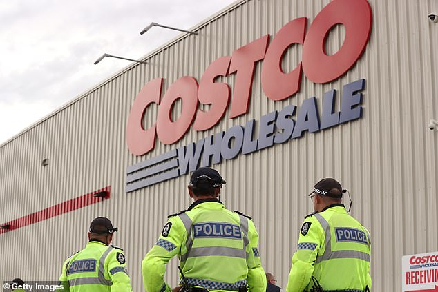 A police presence is seen as customers line up waiting to enter Costco Perth on March 19, 2020 in Australia