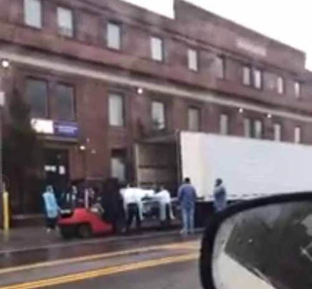 MMedical workers help to slide the bodies on to the truck waiting to carry away the covid-19 corpses in Brooklyn, New York yesterday