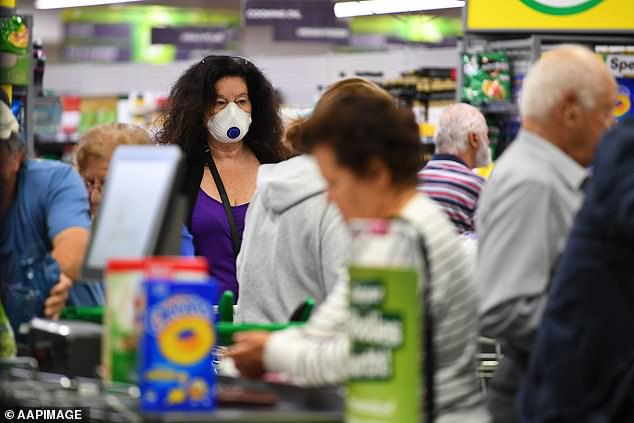 Key businesses like pharmacies and supermarkets would stay open. Pictured: a woman wears a protective mask at a Melbourne Woolworths checkout