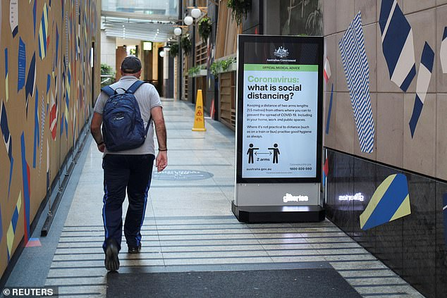 A man walks near a sign in Sydney on Tuesday (pictured) with instructions about social distancing following the implementation of stricter rules to limit the spread of the coronavirus