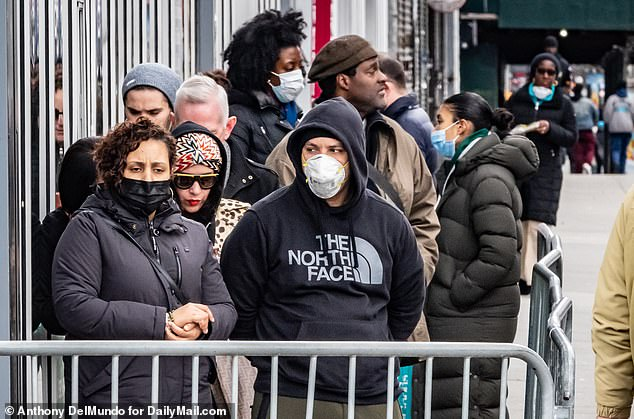 A crowd of people lined up wearing face masks outside a Whole Foods in Harlem, New York on Tuesday