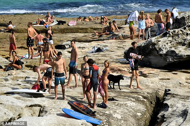 Crowds of sunbathers are spotted on the rocks at Mackenzies Bay in Sydney's east on Tuesday (pictured) despite social distancing rules
