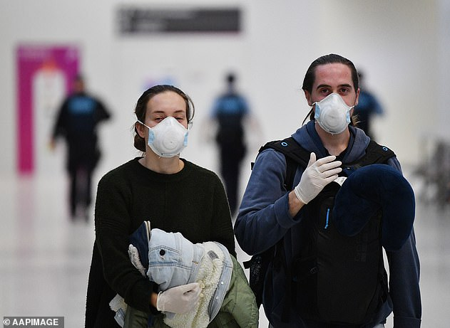 Travellers in face masks at Adelaide airport on Wednesday (pictured) with arrivals from overseas forced into a mandatory 14-day quarantine