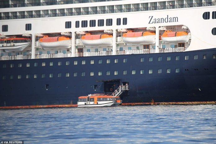 Passengers were seen on lifeboats on the side of the Zaandam on Saturday before heading to the nearby Rotterdam anchored