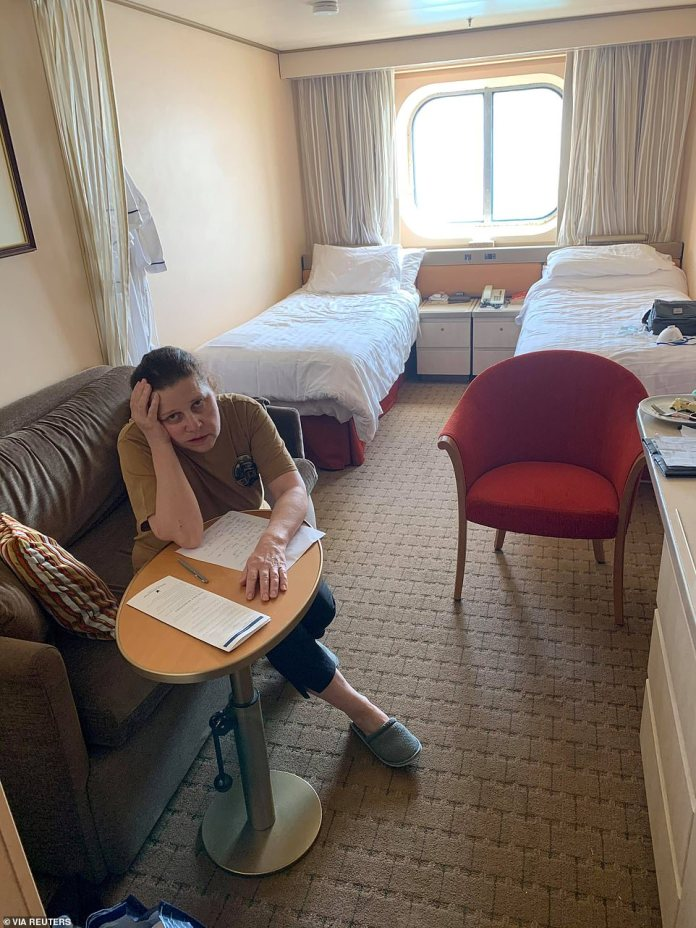"""Canadian passenger Anna Joiner is pictured in her cabin aboard the MS Zaandam last week. Many passengers have complained of being """"imprisoned"""" on ships and their chances of getting coronavirus are increasing by the day"""