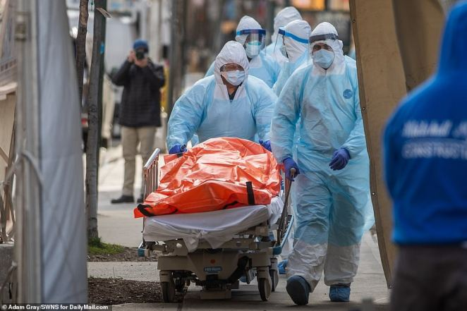 Bodies are loaded onto a refrigerated truck outside of Wyckoff Medical Center, as the number of victims from coronavirus continues to grow on Thursday. There were 911 new deaths recorded in the United State on Thursday