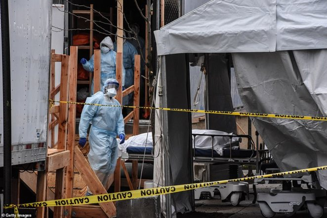Dire: Medical workers move a body into a refrigerated mobile morgue at the Wyckoff Heights Medical Center in Brooklyn