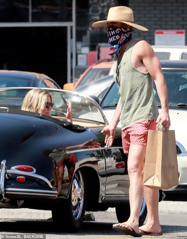 No fuss: Chris looked as if he were ready for a day at the beach with his low-key olive tank top, red patterned shorts, black flip flops and a wide-brimmed straw hat