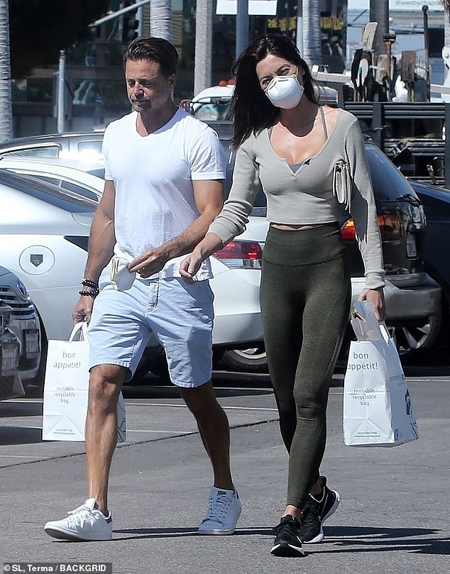 Rock solid: Rykova, 26, showed off her amazingly fit figure in olive green leggings and a long-sleeved crop-top over a sports bra