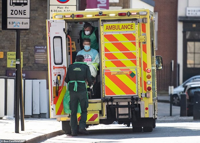 A member of the public is transported by ambulance to Euston, London, by paramedics wearing personal protective clothing and medical masks.