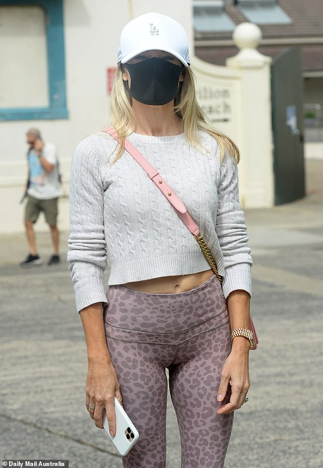 Australians should lean towards not using masks and to instead just stay at home, experts say (pictured: woman wears face mask outside pop-up COVID-19 testing clinic in Bondi)