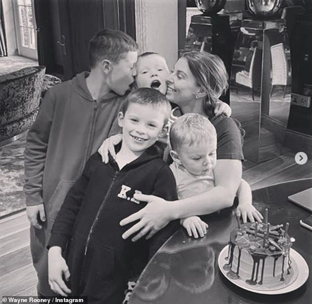 So sweet:Wayne meanwhile shared another black and white snap from this day, this time showing the boys cuddling up to their mum as she wraps her arms around them