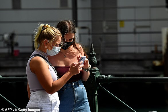 Federal government struggles to produce enough medical supplies as confirmed coronavirus cases reach more than 2,400. Pictured: two young women in masks walk along Circular Quay in Sydney on Wednesday