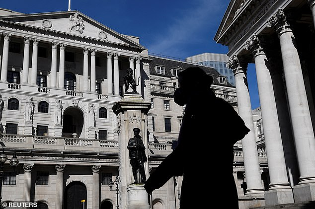 Person wearing mask walks past Bank of England during coronavirus pandemic