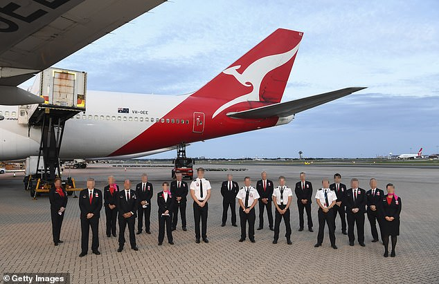 Four Qantas flight attendants have tested positive for coronavirus after being exempt from forced hotel quarantine measures on return from Chile. Pictured: Qantas staff in front of an aircraft that landed from Santiago in March 29