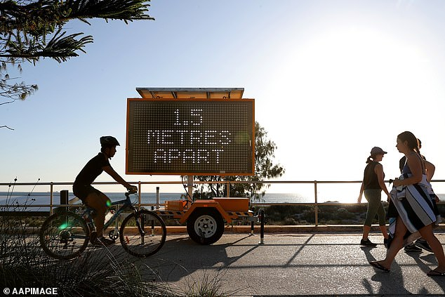 On Tuesday, the government will make public its expert modelling on the spread of coronavirus and the danger of prematurely easing social distancing rules (Members of the public are seen walking past a sign reading '1.5 Metres Apart' in Perth)