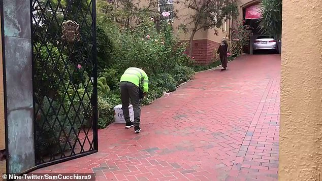 Special delivery: a man deposits a case of wine at the monastery where Cardinal George Pell was to spend his first night of freedom