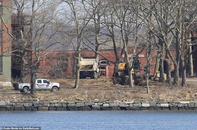 A department of corrections vehicle on Hart Island on Tuesday along with trucks and a back-hoe digging mass graves
