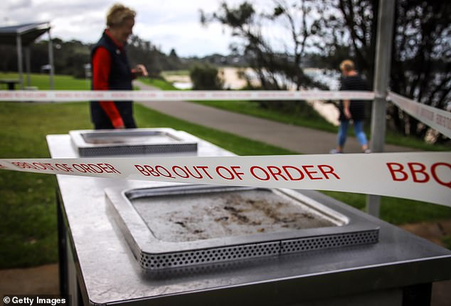 Out of order tape blocks a forlorn barbecue next to Mollymook beach on the NSW South Coast on Wednesday. Public gatherings are limited to two people but everyone is urged to stay home