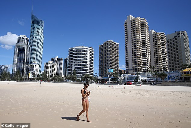 Australia's beaches have been closed due to the coronavirus crisis. A woman is pictured walking to Surfers Paradise on April 7 before the beach closes for the long Easter weekend