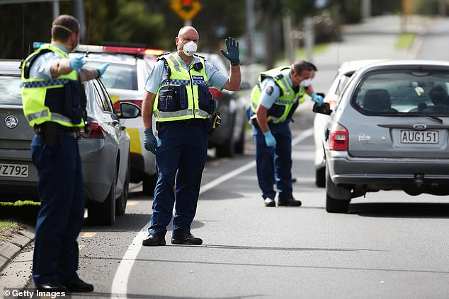 New Zealand blocked due to COVID-19, police (pictured Thursday in Warkworth) set up checkpoints to ensure people on the roads are traveling for essentials