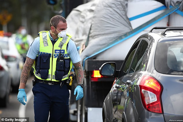 Police in New Zealand are seen stopping vehicles on the state highway at Warkworth on Thursday (pictured), ensuring those travelling are doing so for essential reasons