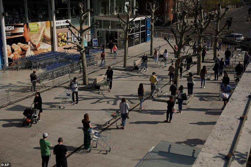 West London: la gente observa el distanciamiento social en un intento de detener la propagación del coronavirus al pararse detrás de las líneas de cinta mientras hacen cola para comprar fuera de una sucursal de la cadena de supermercados Tesco