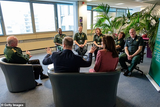 Prince William, Duke of Cambridge and Catherine, Duchess of Cambridge talking with staff, including Chief Executive of the London Ambulance Service, Garrett Emmerson (left) as they visit the London Ambulance Service 111 control room to meet staff who have been taking NHS 111 calls from the public
