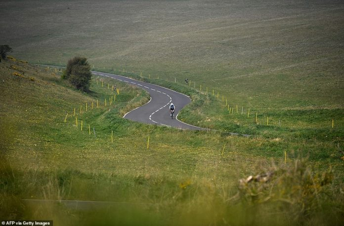 A cyclist bikes along an empty road near Beachy Head near Eastbourne on Sunday morning. Although a minority of people continue to ignore the lock rules, the public generally adheres to government directives to stay indoors, except for essential travel