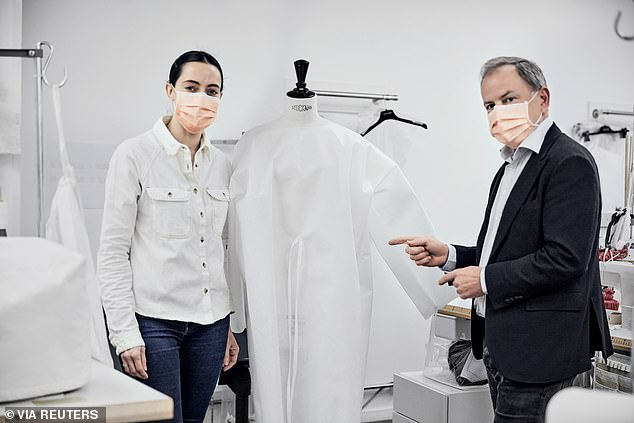 Michael Burke (right), CEO of Louis Vuitton shows a protective gown, while the company makes PPE masks and gowns to fight against coronavirus