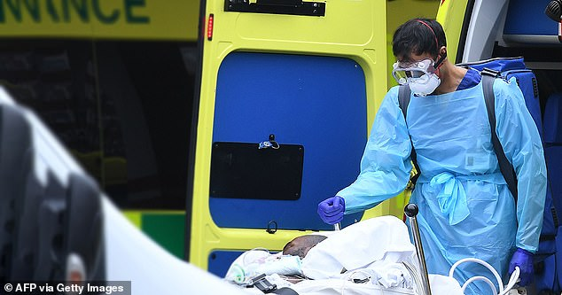 A PPE healthcare professional, including gloves, eye protection and a face mask as a precaution against Covid-19, carries a tank when a patient is transported from an ambulance to St Thomas Hospital in the north london