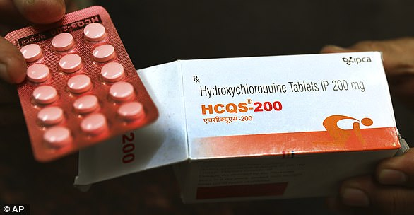 In this April 9 archive photo, a chemist displays hydroxychloroquine tablets in New Delhi, India