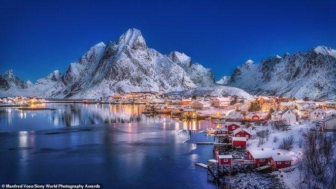 This dreamy image was snapped by German photographer Manfred Voss and was shortlisted in the travel category. Manfred said: 'The small fishing village of Reine in Norway delivers one of the most beautiful views in the Lofoten archipelago. The balance between the cool light of blue hour and the warmth of the well-lit houses was perfect on this particular morning. It was almost windless, resulting in a beautiful reflection of the mountain in the water. I opted for an exposure that balanced the blue hour with the slightly illuminated mountains and the nice light from the houses'