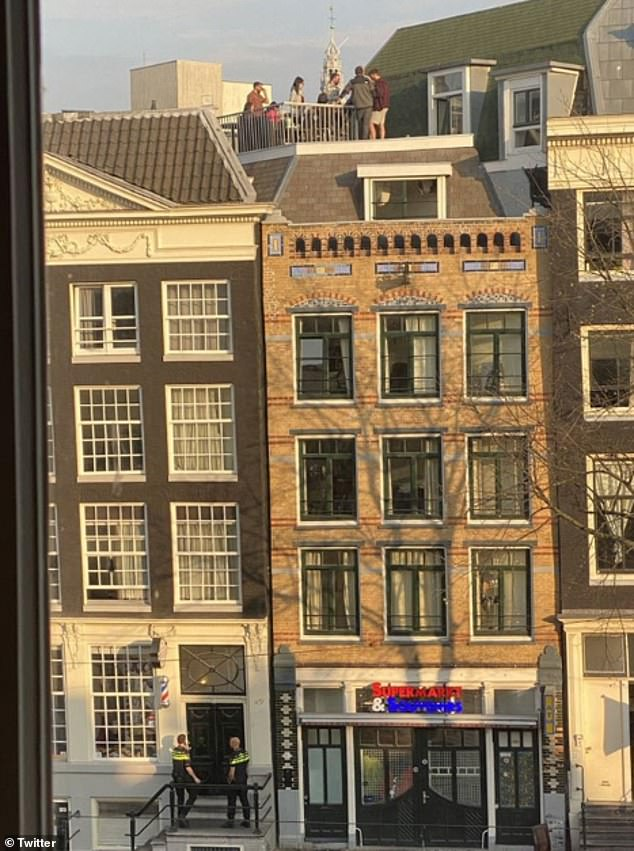 These revellers on a rooftop in Amsterdam are moments away from being shut down by the police, who can be seen by the front door