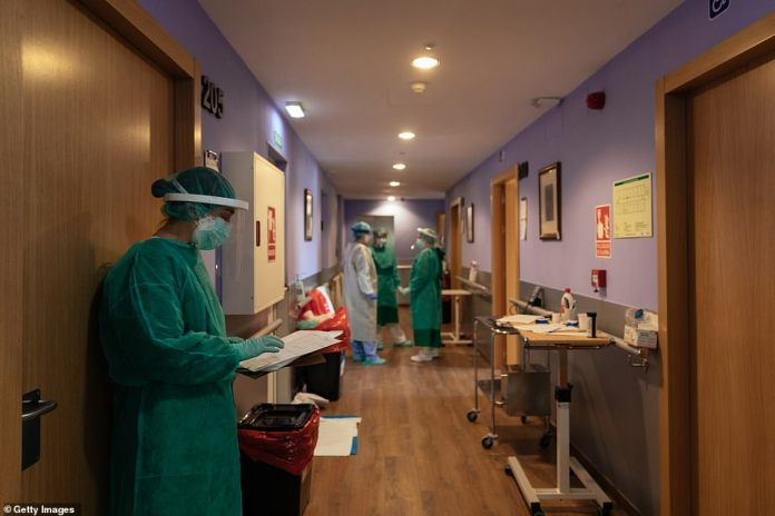Medical staff meet for a briefing in the hallway of a nursing home in Huesca, Spain, where 46 patients with coronavirus were treated on April 16