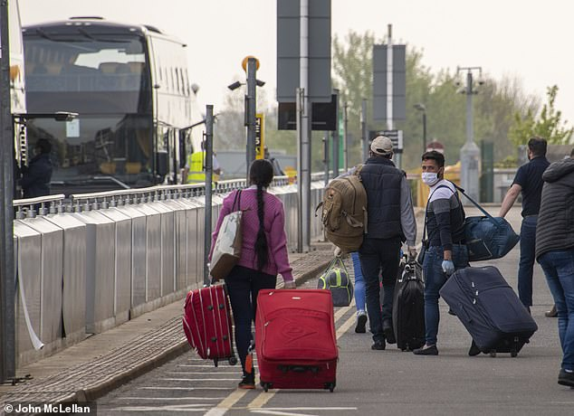 Workers move their luggage to buses before traveling to East Anglia