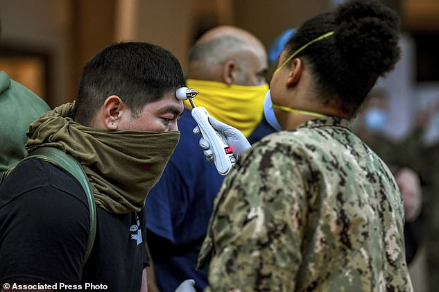 In this April 7, 2020, photo, released by the U.S. Navy, sailors assigned to the aircraft carrier USS Theodore Roosevelt, who have tested negative for COVID-19 and are asymptomatic, are checked at local hotels in Guam in an effort to implement social distancing