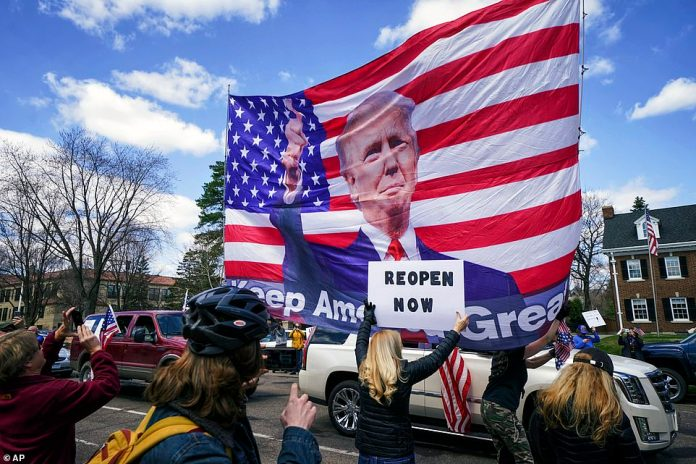 One of the protesters displayed a large banner on Friday representing the image of Trump over the American flag in St. Paul.