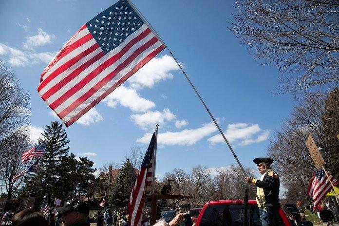 Un homme vêtu de vêtements de style colonial agite un drapeau en l'air et souffle un airhorn à l'arrière d'un camion