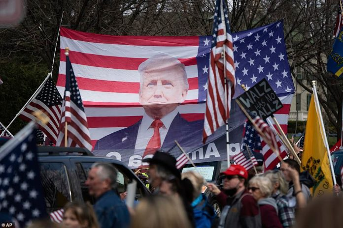 Crowds of protesters applaud as an American flag bearing the President's image is displayed during the demonstration in Saint Paul on Friday