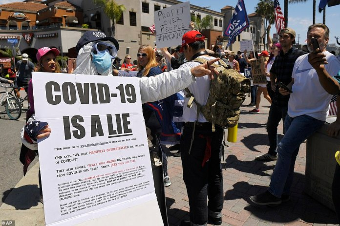 Protesters gathered in the streets (photo, Huntington Beach, California) waving huge American flags and called for the reopening of the country despite the pandemic tearing the country apart.