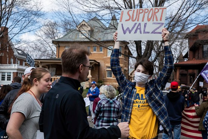 A supporter of the Democratic Governor confronts protesters who oppose the locking of the coronavirus in Saint Paul on Friday