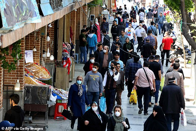 Iranians, some wearing protective gear amid the coronavirus pandemic, shop on a street in the Grand Bazaar market in Tehran. The bazaar will remain closed (April 18, 2020)