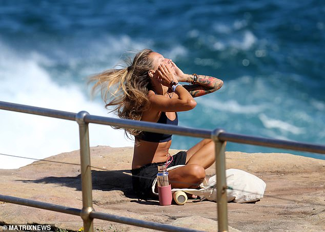 Strict laws that have seen people fined for eating a kebab on a park bench, sunbathing (pictured in Sydney's east on Saturday), or going for a drive will likely be the first rules gone