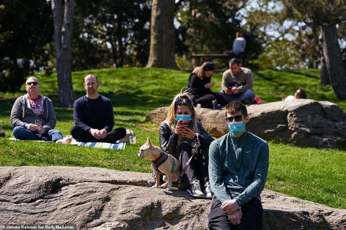 People are seen seated together in pairs in Central Park. Some wore masks while others decided to do without them