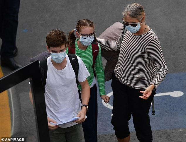Travellers wearing face masks are seen boarding buses at Adelaide Airport on Monday