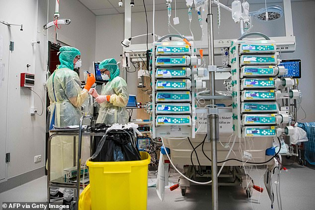 Nurses wearing masks and protective gear work in a ward at the Karolinska hospital in Solna yesterday, with Sweden planning to ramp up testing for the coronavirus