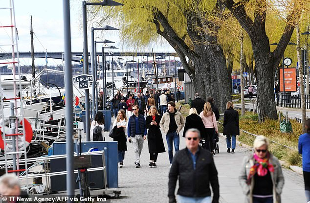 People walk on a pedestrian street in Stockholm yesterday, in one of the few developed countries which has not closed bars and restaurants or eliminated public gatherings